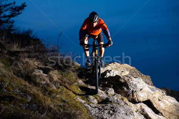 Enduro Cyclist Riding the Bike on the Rock at Night. Extreme Sport Concept. Space for Text. Stock photo © maxpro