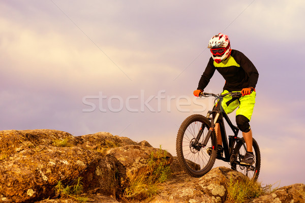 Professional Cyclist Riding the Bike on the Top of the Rock. Extreme Sport Concept. Space for Text. Stock photo © maxpro
