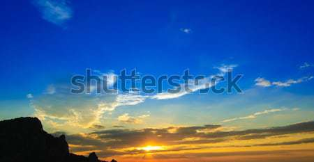 Beautiful Sunset with Clouded Orange Sky and Mountain Silhouette Stock photo © maxpro