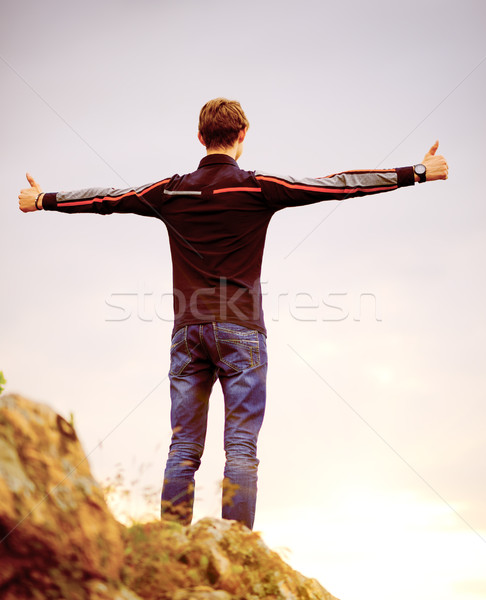 Young Man Standing on Mountain Peak with Arms Raised. Active Lifestyle Concept. Stock photo © maxpro