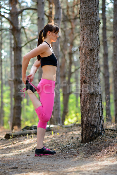 Young Fitness Woman Stretching her Legs in the Pine Forest. Female Runner Doing Stretches . Healthy  Stock photo © maxpro