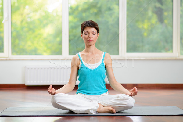 Yoga and Meditation Indoors. Young Woman Sitting on Lotus Position and Meditating with Eyes Closed. Stock photo © maxpro