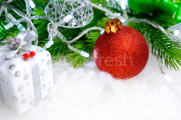 Christmas Decoration with Red Ball, Green Fir Branch and White Lights in Snow. Greeting Card Stock photo © maxpro