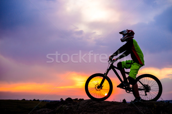 Professional Cyclist Resting with Down Hill Bike on the Rock at Sunset. Extreme Sport. Stock photo © maxpro