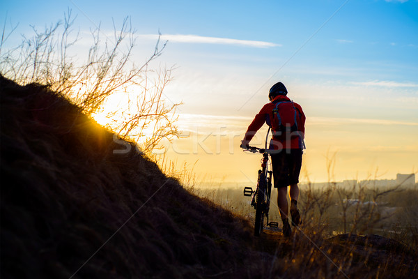 Silhouette of Enduro Cyclist with Mountain Bike on the Rocky Trail at Sunset. Active Lifestyle Conce Stock photo © maxpro