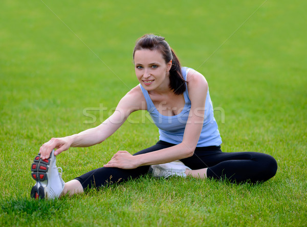 Stock photo: Beautiful Smiling Woman Doing Stretching Exercise on the Grass in the Park