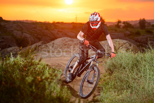 Professional Cyclist Riding the Bike on the Mountain Rocky Trail at Sunset. Extreme Sport Stock photo © maxpro