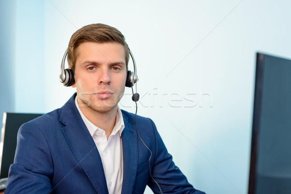 Young Customer Support Phone Operator with Headset at his Working Place in Office. Stock photo © maxpro