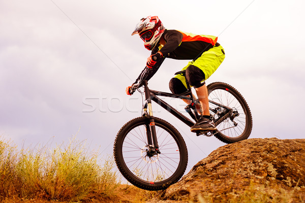 Professional Cyclist Riding the Bike Down Rocky Hill. Extreme Sport Concept. Space for Text. Stock photo © maxpro