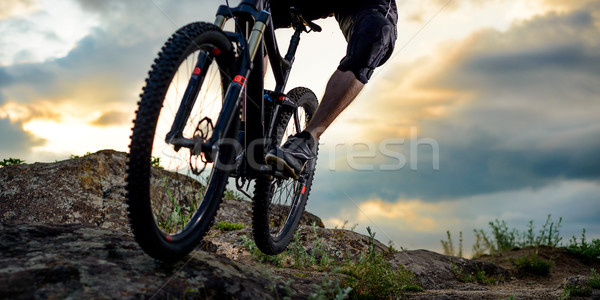 Stock photo: Professional Cyclist Riding the Bike Down Rocky Hill at Sunset. Extreme Sport. Space for Text.