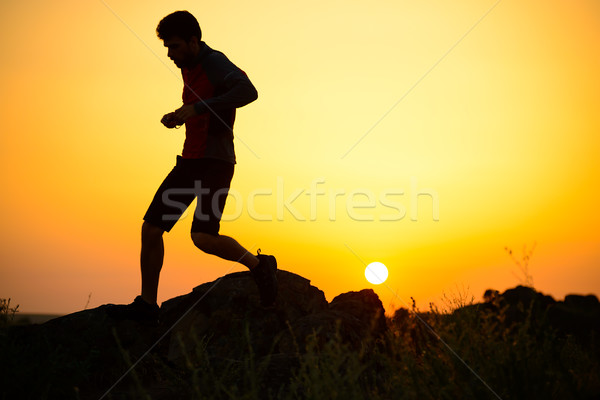 Stock photo: Young Sportsman Running on the Rocky Mountain Trail at Sunset. Active Lifestyle