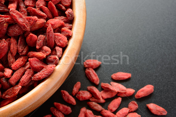 Wooden Bowl Full of Dried Goji Berries on the Black Table Stock photo © maxpro