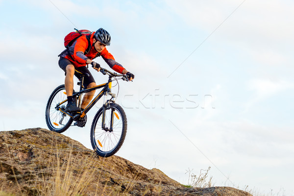Stock photo: Cyclist in Red Jacket Riding the Bike Down Rocky Hill. Extreme Sport.