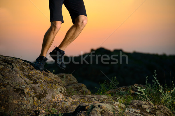 Stock photo: Close-up of Sportsman's Legs Running on the Rocky Mountain Trail at Night. Active Lifestyle