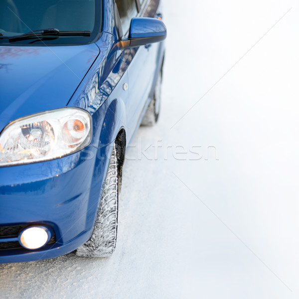 Stock photo: Blue Car with Winter Tires on the Snowy Road. Drive Safe. Space for Text.
