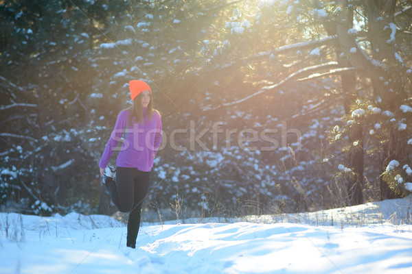 Stock photo: Young Woman Runner Stretching her Legs in Beautiful Winter Forest at Sunny Frosty Day. Active Lifest