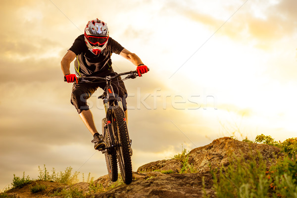 Professional Cyclist Riding the Bike Down Rocky Hill at Sunset. Extreme Sport. Stock photo © maxpro