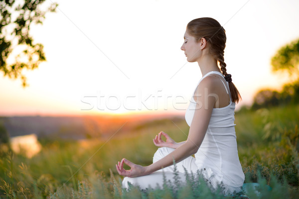 Stock photo: Young Beautiful Woman Practices Yoga on the Sunny Meadow
