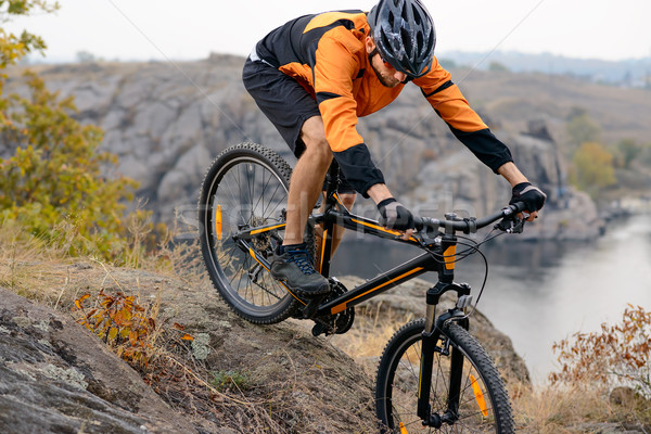 Cyclist in Orange Wear Riding the Bike Down Rocky Hill under River Stock photo © maxpro