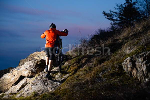 Stock photo: Enduro Cyclist Taking his Bike up the Rocky Trail at Night. Extreme Sport Concept. Space for Text.