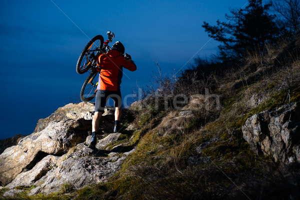 Enduro Cyclist Taking his Bike up the Rocky Trail at Night. Extreme Sport Concept. Space for Text. Stock photo © maxpro