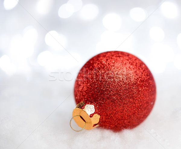 Christmas Decoration with Red Ball in the Snow on the Blurred Background with Holiday Lights. Greeti Stock photo © maxpro