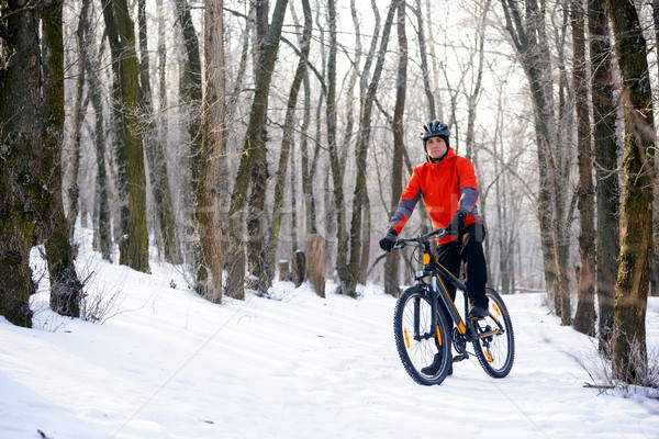 Mountain Biker Resting Bike on the Snowy Trail in Beautiful Winter Forest Stock photo © maxpro