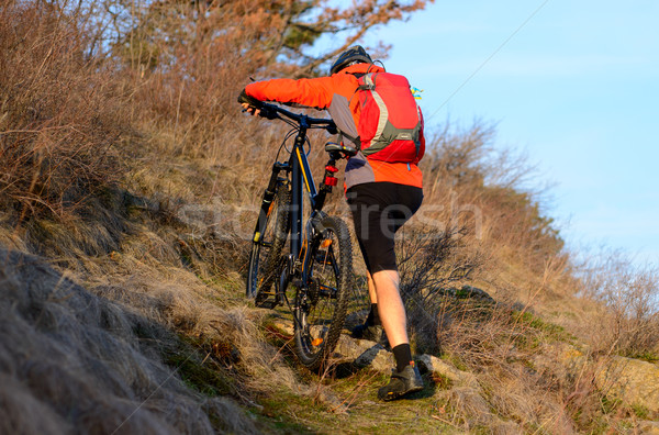Enduro Cyclist Taking his Mountain Bike Up the Rocky Trail. Extreme Sport Concept. Space for Text. Stock photo © maxpro