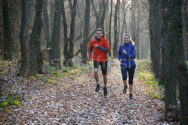 Young Couple Running on the Trail in the Wild Forest Stock photo © maxpro