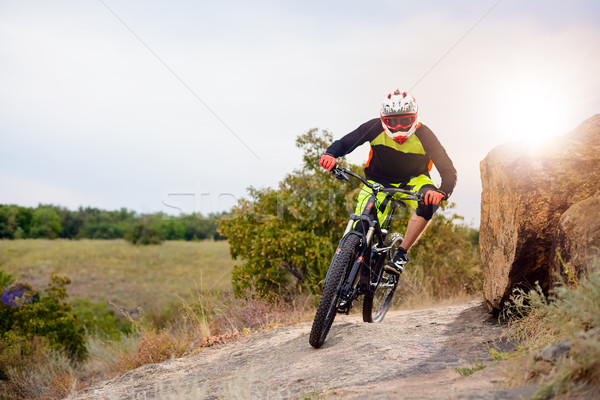 Professional Cyclist Riding the Bike at the Rocky Trail. Extreme Sport Concept. Space for Text. Stock photo © maxpro