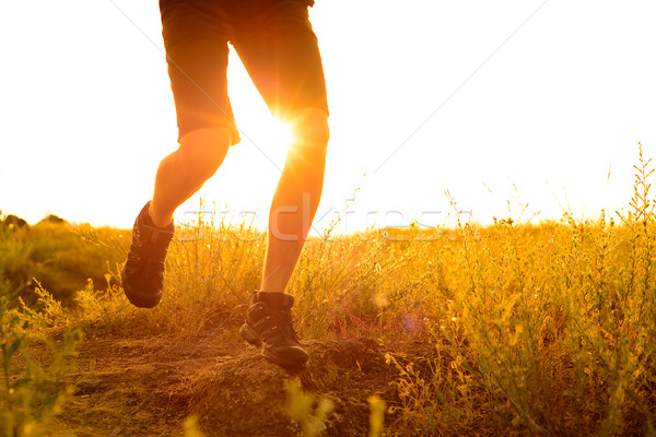Stock photo: Close-up of Sportsman's Legs Running on the Rocky Mountain Trail at Sunset. Active Lifestyle