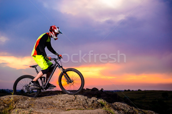 Professional Cyclist Riding the Bike on the Rock at Sunset. Extreme Sport Concept. Space for Text. Stock photo © maxpro