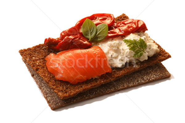 Bread crisp with salmon, soft cheese, dried tomatoes and chervil Stock photo © maxsol7