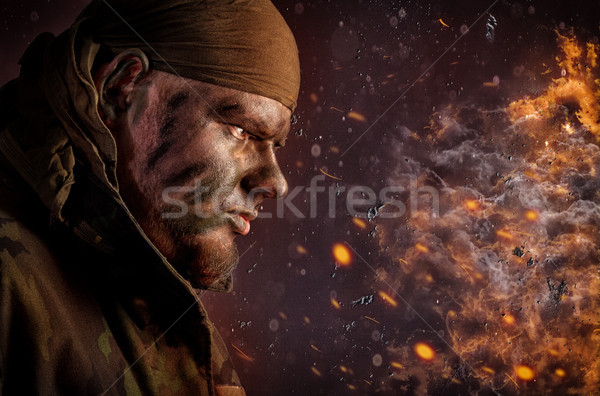 Young man in camouflage paint and a coat Stock photo © Mazirama