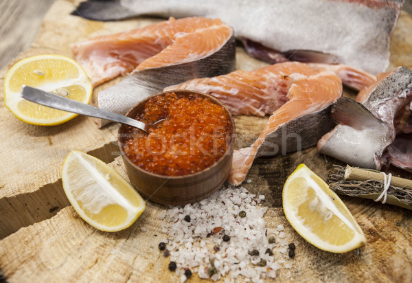 Fresh Norwegian rainbow trout with lemon red caviar, sea salt and onions on a wooden background Stock photo © mcherevan