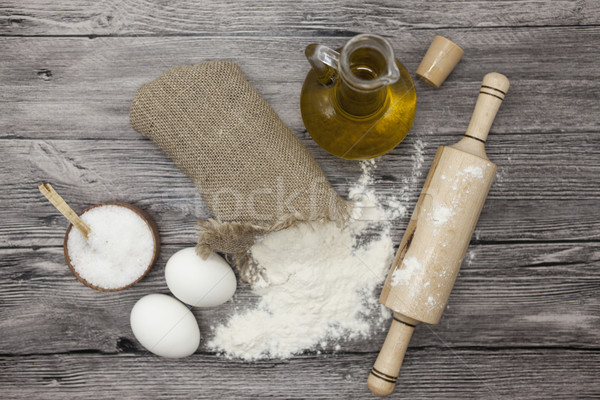 Wheat flour in a canvas bag, the olive oil in a glass carafe, a large salt shaker wood, raw eggs, a  Stock photo © mcherevan