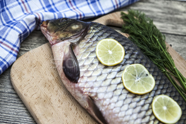 A large fresh carp live fish lying on a wooden board with a knife and slices of lemon and with salt  Stock photo © mcherevan