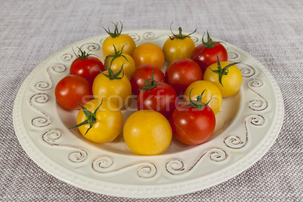 Fresh red and yellow cherry tomatoes on a porcelain plate in a rustic style Stock photo © mcherevan