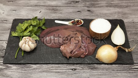 Pieces of fresh raw beef liver, onion, garlic, spices, salt on the stone plate on a white background Stock photo © mcherevan