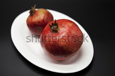 Two fruit juicy Spanish pomegranate on porcelain plate on a dark background Stock photo © mcherevan