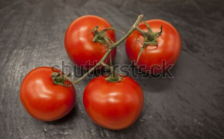 Stock photo: Fresh branch of red Sicilian ripe tomatoes on a stone background