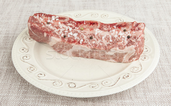 A piece of fresh marbled beef with sea salt and black pepper on the porcelain plate Stock photo © mcherevan