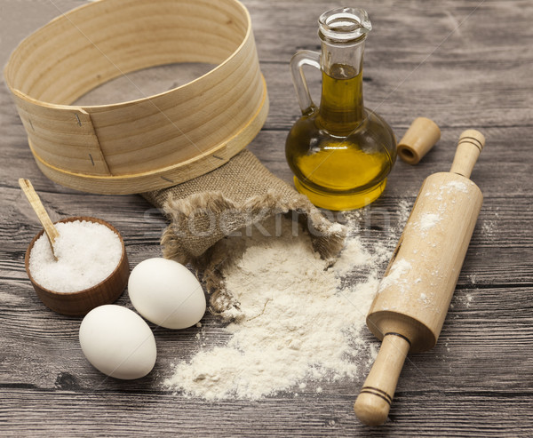 Wheat flour in a canvas bag,sieve, the olive oil in a glass carafe, a large salt shaker wood, raw eg Stock photo © mcherevan