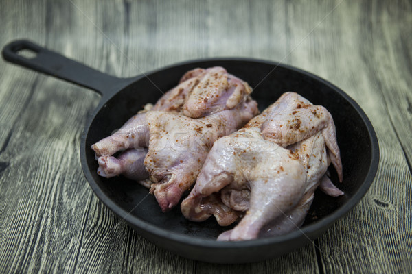 Two raw fresh chicken on iron pan  over wooden background. Stock photo © mcherevan