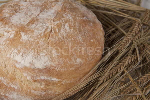 White loaf of homemade bread on a table with rye spikelets and oats. Stock photo © mcherevan