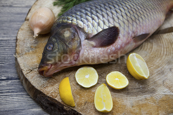 Stock photo: Fresh raw fish carp caught lying on a wooden stump with a knife and slices of lemon and with salt di