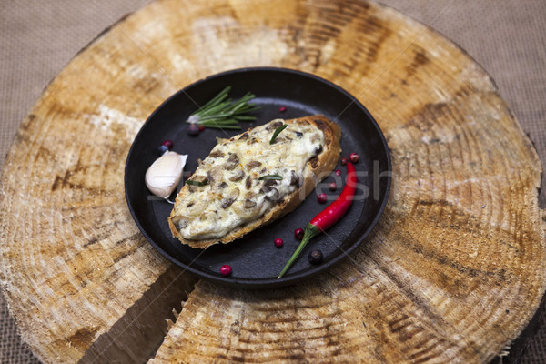 Home baked hot sandwich with mushrooms, cheese, onion on a cast-iron pan on a wooden background. Stock photo © mcherevan