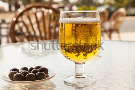 Misted glass of beer with olives on a glass table Stock photo © mcherevan