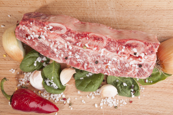 Close-up piece of fresh marbled beef, chili pepper, parsley, onion, garlic, ribs lie on a wooden tra Stock photo © mcherevan