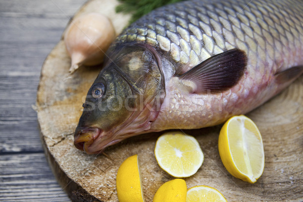 Fresh raw fish carp caught lying on a wooden stump with a knife and slices of lemon and with salt di Stock photo © mcherevan